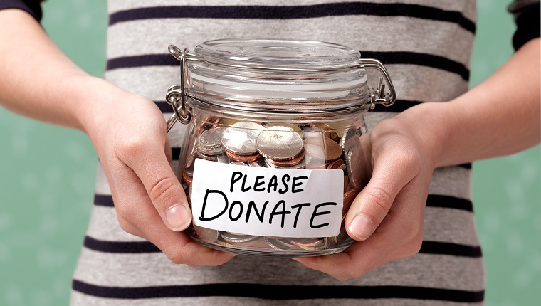 Close up of a girl holding a charity donation jar with coins in.
