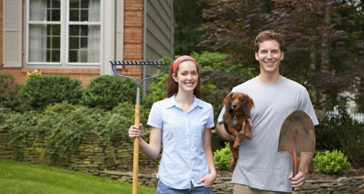 Young couple holding dog and garden tools