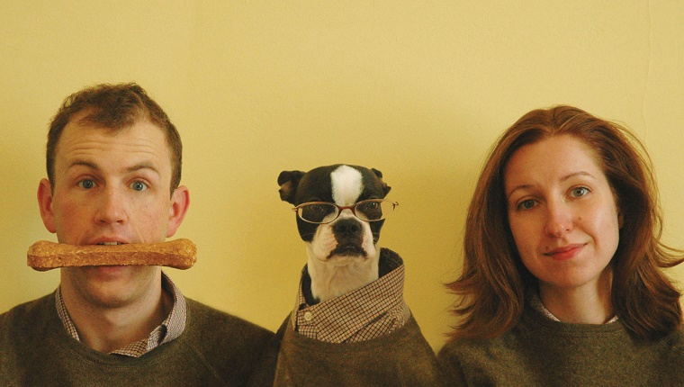 Humorous Christmas card portrait of man, woman, and Boston Terrier pet dog. Dog takes on human attribute of wearing glasses, man in turn has dog bone in mouth. Woman is bemused by entire affair. Family dressed in matching sweaters and shirts.